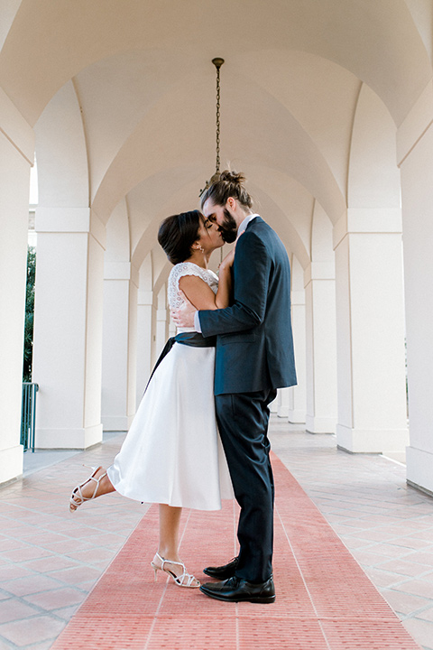 Pasadena-city-hall-styled-shoot-bride-and-groom-kissing-bride-has-her-leg-up-in-a-short-tulle-gown-with-cap-sleeves-and-groom-in-a-navy-tuxedo-with-a-blacl-shawl-lapel