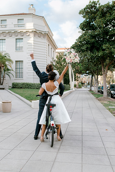 Pasadena-city-hall-styled-shoot-bride-and-groom-on-bike-bride-in-a-short-gown-with-straps-and-groom-in-a-navy-shawl-lapel-tuxedo