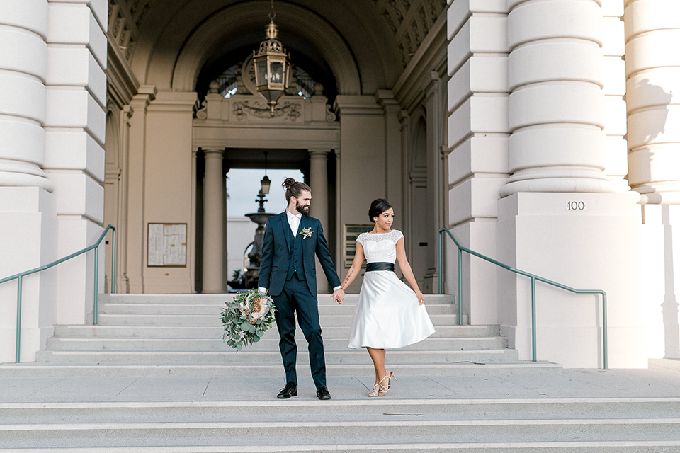 Pasadena-city-hall-styled-shoot-bride-and-groom-on-steps-bride-in-a-short-dress-with-cap-sleeves-groom-in-a-navy-shawl-lapel-tuxedo-with-an-undone-light-blue-bow-tie