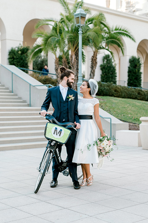 Pasadena-city-hall-styled-shoot-bride-and-groom-standing-next-to-bike-bride-in-a-short-tulle-gown-with-cap-sleeves-and-groom-in-a-navy-tuxedo-with-a-blacl-shawl-lapel