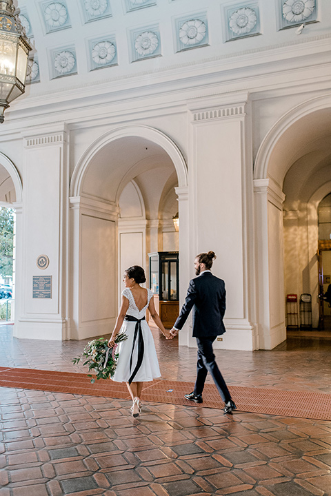 Pasadena-city-hall-styled-shoot-bride-and-groom-walking-away-bride-in-a-short-gown-with-straps-and-groom-in-a-navy-shawl-lapel-tuxedo