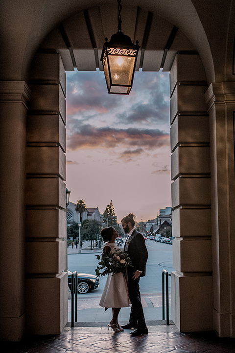 Pasadena-city-hall-styled-shoot-bride-and-groom-with-the-sunset-bride-in-a-short-gown-with-straps-and-groom-in-a-navy-shawl-lapel-tuxedo
