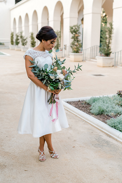 Pasadena-city-hall-styled-shoot-bride-looking-at-flowers-wearing-a-tea-length-gown-with-a-cap-sleeve-and-hair-in-a-low-bun