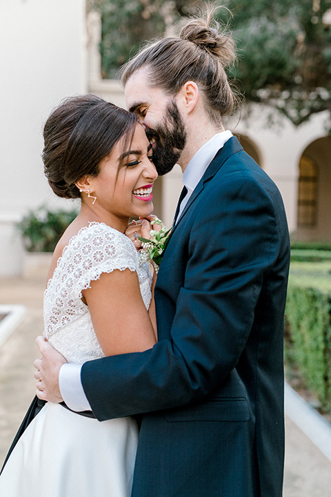 Pasadena-city-hall-styled-shoot-groom-holding-bride-bride-smiling-bride-in-a-short-tulle-gown-with-cap-sleeves-and-groom-in-a-navy-tuxedo-with-a-blacl-shawl-lapel