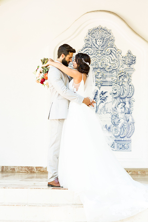rancho-las-lomas-spring-shoot-bride-and-groom-sitting-on-steps-bride-in-a-tulle-a-line-gown-with-straps-and-a-deep-v-neckline-groom-in-a-light-grey-suit-with-a-floral-tie
