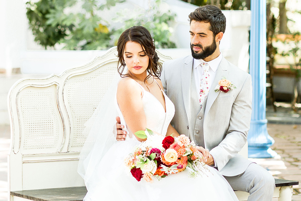 rancho-las-lomas-spring-shoot-bride-and-groom-sitting-on-bench-bride-in-an-a-line-dress-with-straps-groom-in-a-light-grey-suit-with-a-white-floral-tie
