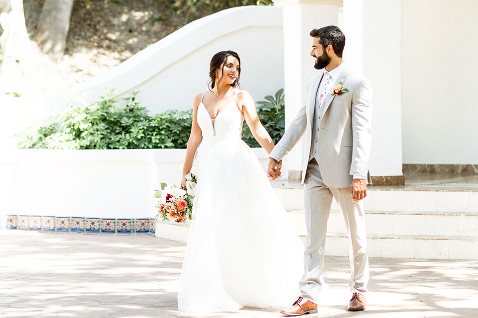 rancho-las-lomas-spring-shoot-bride-and-groom-walking-bride-in-an-a-line-dress-with-straps-groom-in-a-light-grey-suit-with-a-white-floral-tie