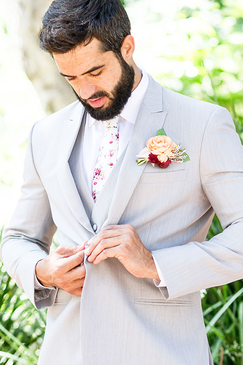 rancho-las-lomas-spring-shoot-groom-buttoning-his-light-grey-suit-coat-with-a-floral-tie
