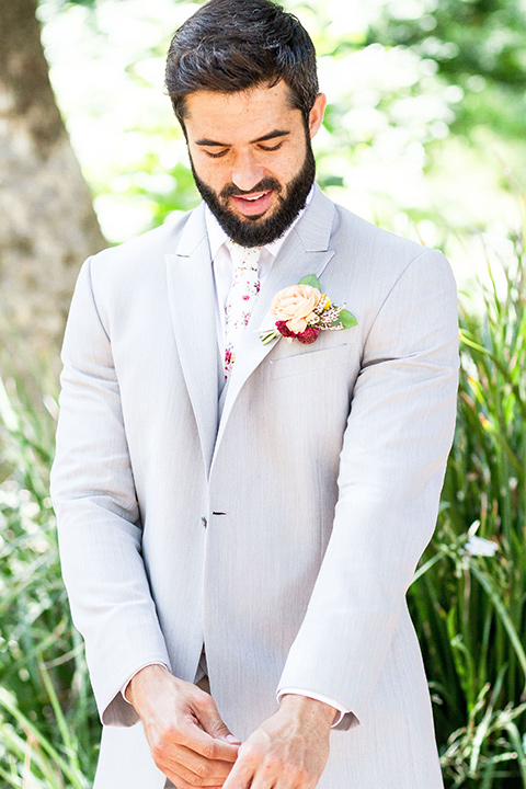 rancho-las-lomas-spring-shoot-groom-fixing-sleeve-in-a-light-grey-suit-with-a-floral-tie