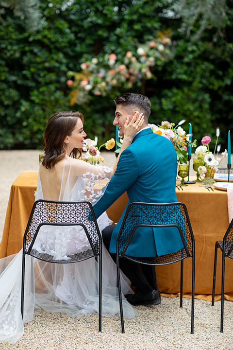 bride and groom at table, bride in a following white gown with a sheer cape and floral design, the groom in a teal tuxedo coat with black pants and a black bow tie