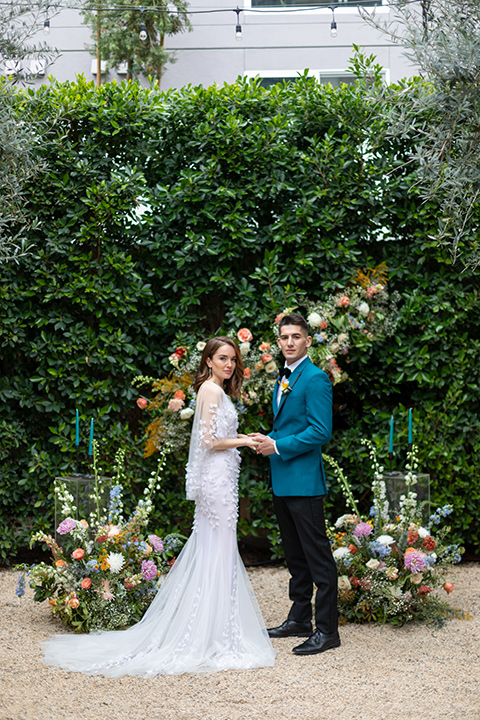bride and groom at ceremony, bride in a following white gown with a sheer cape and floral design, the groom in a teal tuxedo coat with black pants and a black bow tie
