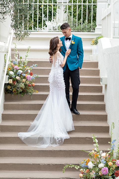bride and groom standing on steps, bride in a following white gown with a sheer cape and floral design, the groom in a teal tuxedo coat with black pants and a black bow tie