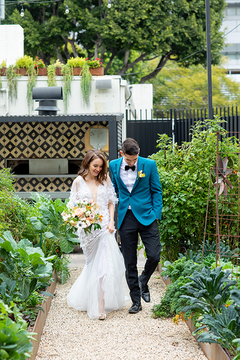 bride and groom walking in the garden, bride in a following white gown with a sheer cape and floral design, the groom in a teal tuxedo coat with black pants and a black bow tie