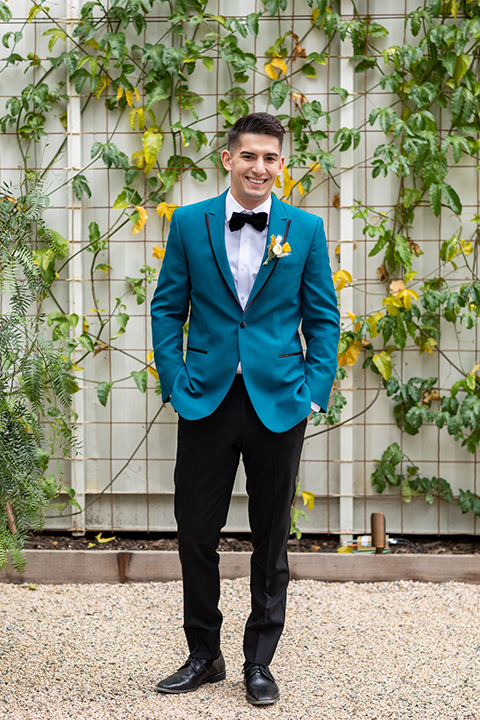 the groom in a teal tuxedo coat with black pants and a black bow tie