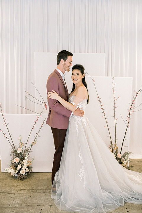 Romatic-Wedding-at-the-ACE-bride-and-groom-at-ceremony-space-in-a-blush-toned-tulle-gown-with-a-sweetheart-neckline-and-an-off-the-shoulder-detail-groom-in-a-rose-pink-jacket-and-deep-burgundy-pant-with-a-velvet-bow-tie