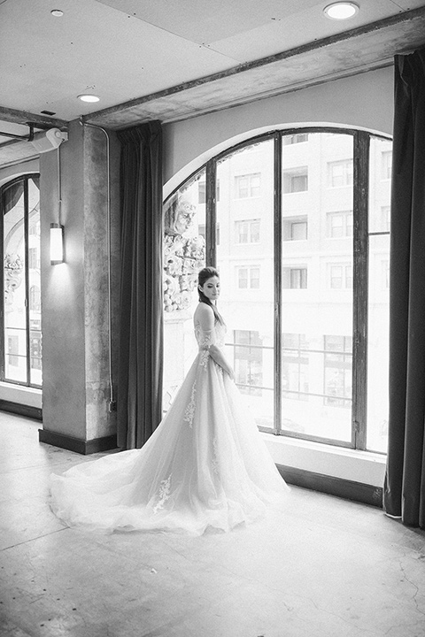 Romatic-Wedding-at-the-ACE-bride-by-window-in-a-blush-toned-tulle-gown-with-a-sweetheart-neckline-with-an-off-the-shoulder-detail