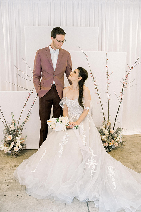 Romatic-Wedding-at-the-ACE-bride-sitting-groom-standing-bride-in-a-blush-toned-tulle-gown-with-a-sweetheart-neckline-with-an-off-the-shoulder-detail-groom-in-a-rose-pink-suit-coat-and-burgundy-pants