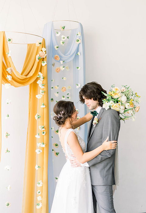 Spring-styled-shoot-bride-and-groom-at-ceremony-space-bridal-gown-with-a-open-back-and-lace-cap-sleeves-and-soft-tulle-skirt-the-groom-is-in-a-grey-suit-with-a-green-velvet-bowtie