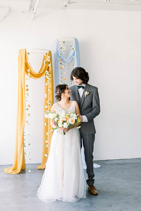 Spring-styled-shoot-bride-and-groom-looking-at-each-other-at-ceremony-space-in-a-bridal-gown-with-a-open-back-and-lace-cap-sleeves-and-soft-tulle-skirt-groom-is-wearing-a-grey-suit-with-a-green-velvet-bow-tie
