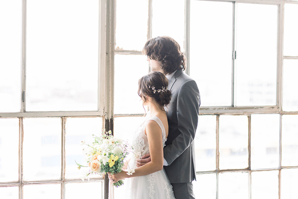 Spring-styled-shoot-bride-and-groom-looking-out-windows-the-bride-wearing-a-soft-tulle-gown-with-a-lace-sweetheart-neckline-and-a-soft-tulle-skirt-the-groom-in-a-grey-suit-with-a-deep-green-velvet-bow-tie