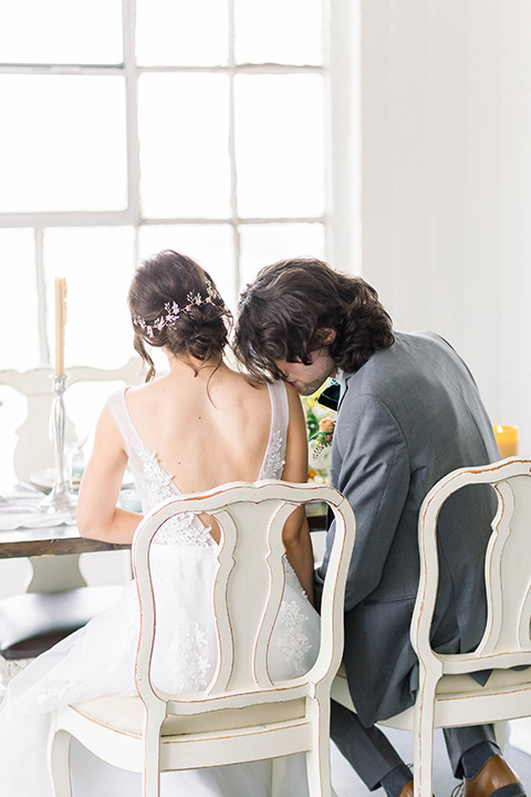 Spring-styled-shoot-bride-and-groom-sitting-at-table-bridal-gown-with-a-open-back-and-lace-cap-sleeves-and-soft-tulle-skirt-the-groom-is-in-a-grey-suit-with-a-green-velvet-bowtie