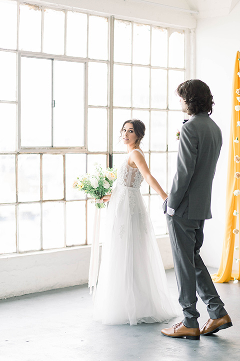 Spring-styled-shoot-bride-and-groom-walking-by-window-the-bride-in-a-gown-with-a-open-back-and-lace-cap-sleeves-and-soft-tulle-skirt-groom-is-wearing-a-grey-suit-with-a-green-velvet-bow-tie