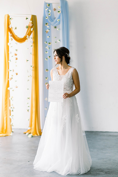 Spring-styled-shoot-bride-standing-bridal-gown-with-a-open-back-and-lace-cap-sleeves-and-soft-tulle-skirt