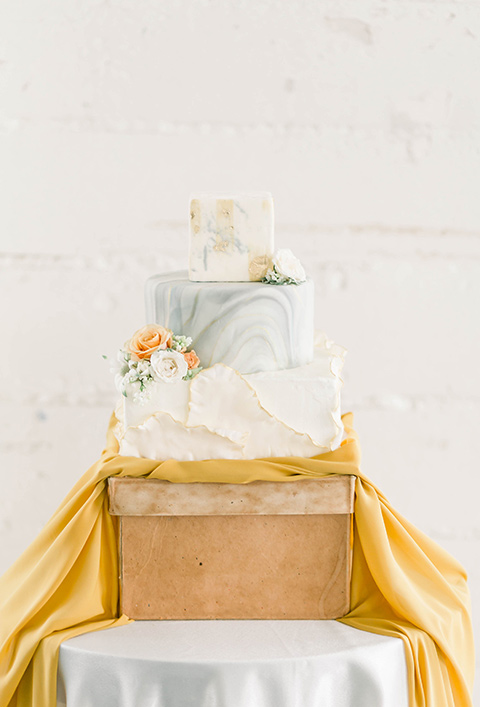Spring-styled-shoot-cake-in-a-three-tier-style-with-light-blue-and-white-fondant-and-yellow-flowers