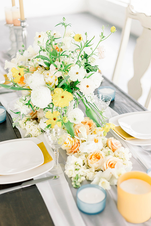 Spring-styled-shoot-decor-on-the-table-with-white-linens-and-yellow-and-blue-candles-and-crystal