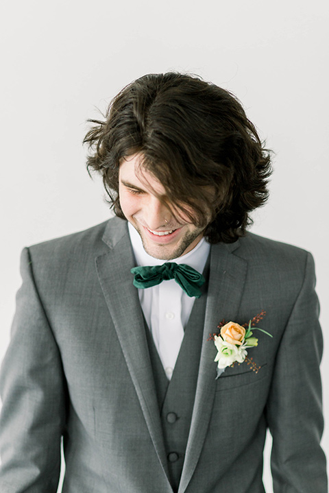 Spring-styled-shoot-groom-close-up-in-a-grey-suit-with-a-green-velvet-bowtie
