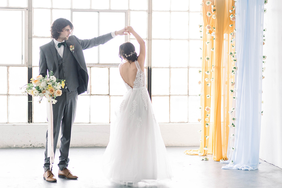 Spring-styled-shoot-groom-twirling-bride-the-bride-wearing-a-soft-tulle-gown-with-a-lace-sweetheart-neckline-and-a-soft-tulle-skirt-the-groom-in-a-grey-suit-with-a-deep-green-velvet-bow-tie