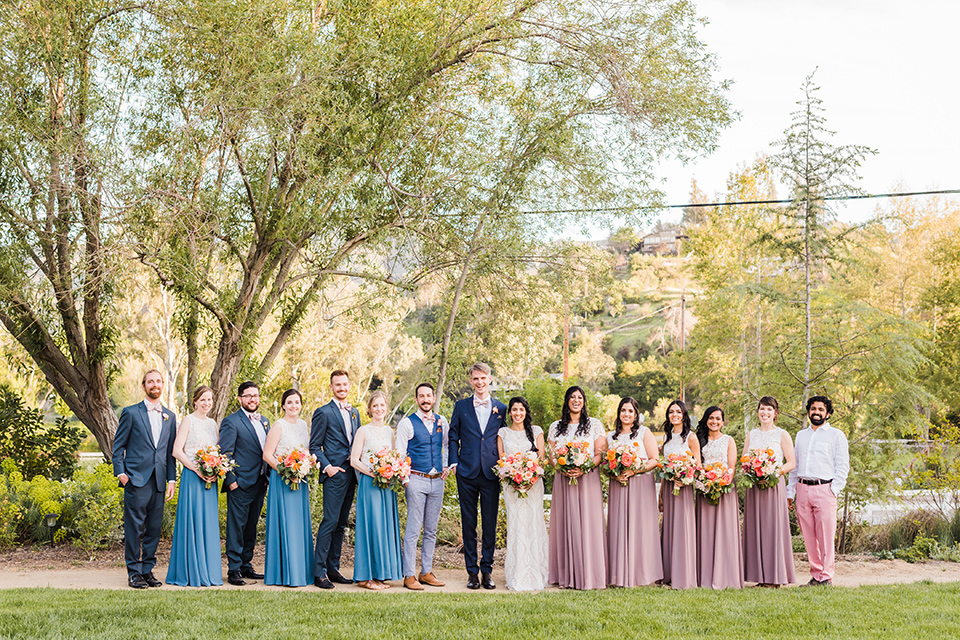 Supriya-and-Chris-wedding-bridal-party-for-traditional-ceremony-the-bridesmaids-in-two-toned-dresses-in-pink-and-blue-the-groomsmen-in-navy-suits-and-the-bride-in-a-white-lace-formfitting-gown-and-the-groom-in-a-navy-suit-with-pink-bow-tie