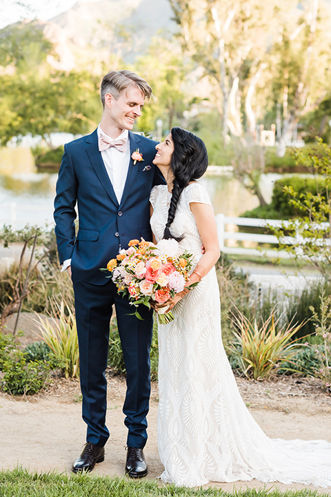 Supriya-and-Chris-wedding-bride-and-groom-looking-at-each-other-the-bride-in-a-white-formfitting-gown-and-the-groom-in-a-navy-suit-with-pink-bow-tie
