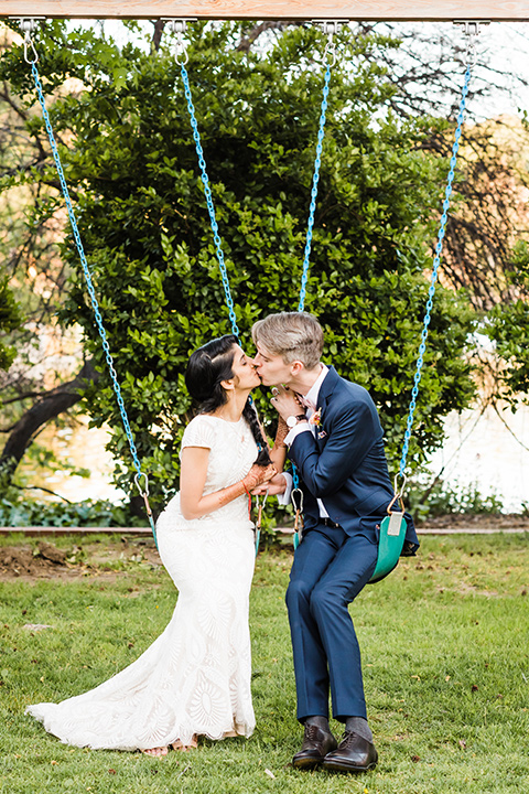 Supriya-and-Chris-wedding-bride-and-groom-on-swings-the-bride-in-a-lace-gown-and-the-groom-in-a-navy-suit-with-pink-bow-tie