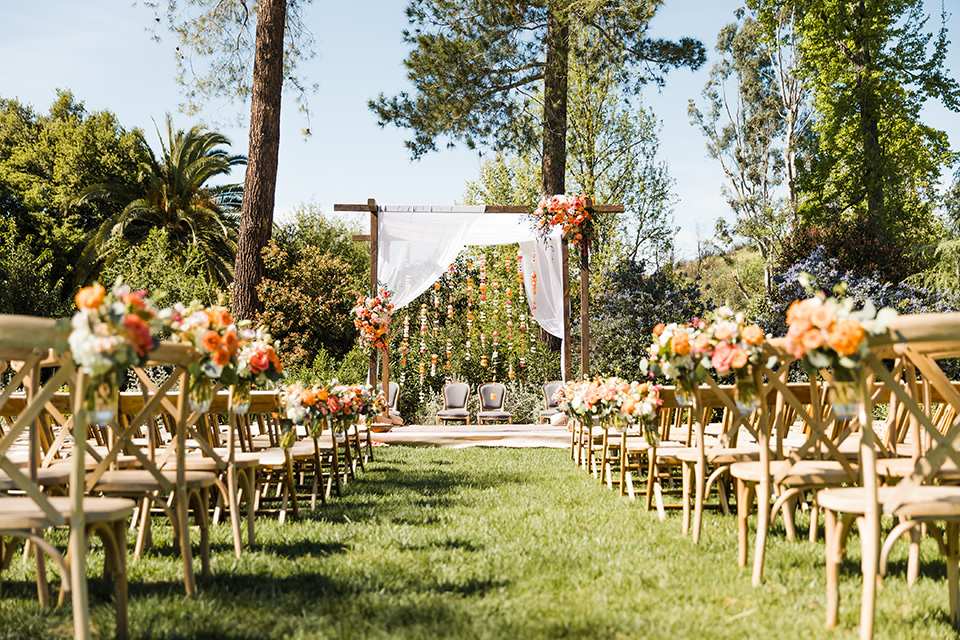 Supriya-and-Chris-wedding-ceremony-set-up-with-wooden-chairs-and-orange-and-yellow-flowers