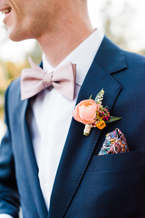 Supriya-and-Chris-wedding-close-up-on-groom-attire-with-a-navy-suit-and-pink-bow-tie