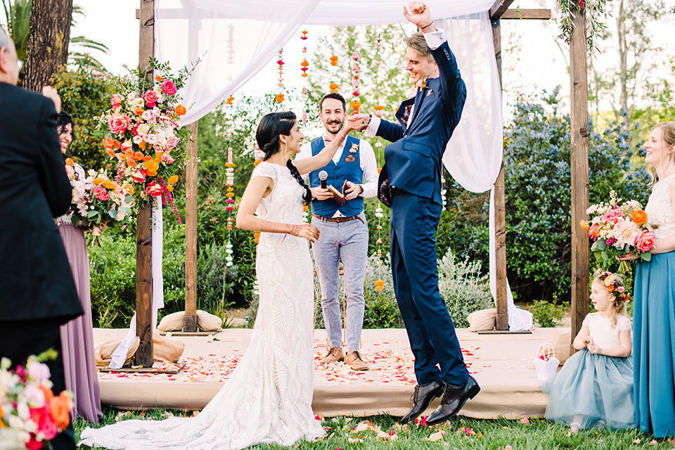 Supriya-and-Chris-wedding-groom-jumping-at-ceremony-the-bride-is-in-a-white-formfitting-gown-with-lace-and-thin-straps-the-groom-in-a-blue-suit-with-pink-bow-tie
