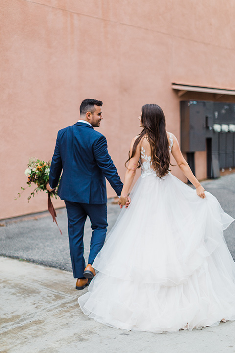 bride in a full tulle ballgown with a crystal and lace bodice and straps, groom in a blue suit with a floral tie and brown shoes