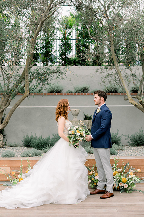 The-Harper-Shoot-bride-and-groom-at-ceremony-bride-in-a-tulle-ballgown-with-a-beaded-bodice-groom-in-a-mix-and-match-look-with-a-blue-jacket-and-grey-pant-and-vest-and-a-blue-long-tie-to-match-the-jacket