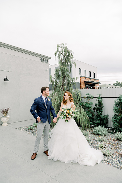 The-Harper-Shoot-bride-and-groom-laughing-looking-at-each-other-bride-in-a-tulle-ballgown-with-a-beaded-bodice-groom-in-a-mix-and-match-look-with-a-blue-jacket-and-grey-pant-and-vest-and-a-blue-long-tie-to-match-the-jacket