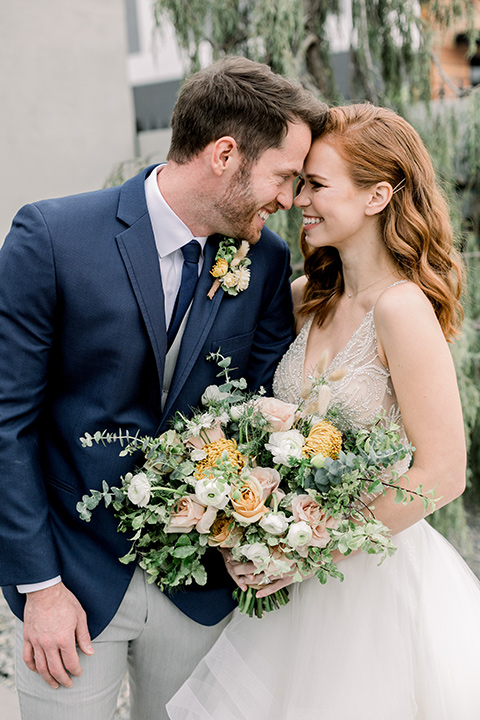 The-Harper-Shoot-bride-and-groom-touching-heads-bride-in-a-tulle-ballgown-with-a-beaded-bodice-groom-in-a-mix-and-match-look-with-a-blue-jacket-and-grey-pant-and-vest-and-a-blue-long-tie-to-match-the-jacket