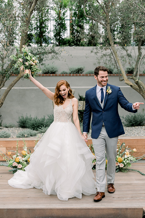 The-Harper-Shoot-bride-and-groom-walking-down-aisle-bride-in-a-tulle-ballgown-with-a-beaded-bodice-groom-in-a-mix-and-match-look-with-a-blue-jacket-and-grey-pant-and-vest-and-a-blue-long-tie-to-match-the-jacket