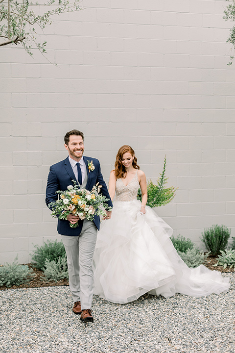 The-Harper-Shoot-bride-and-groom-walking-towards-camera-bride-in-a-tulle-ballgown-with-a-beaded-bodice-groom-in-a-mix-and-match-look-with-a-blue-jacket-and-grey-pant-and-vest-and-a-blue-long-tie-to-match-the-jacket