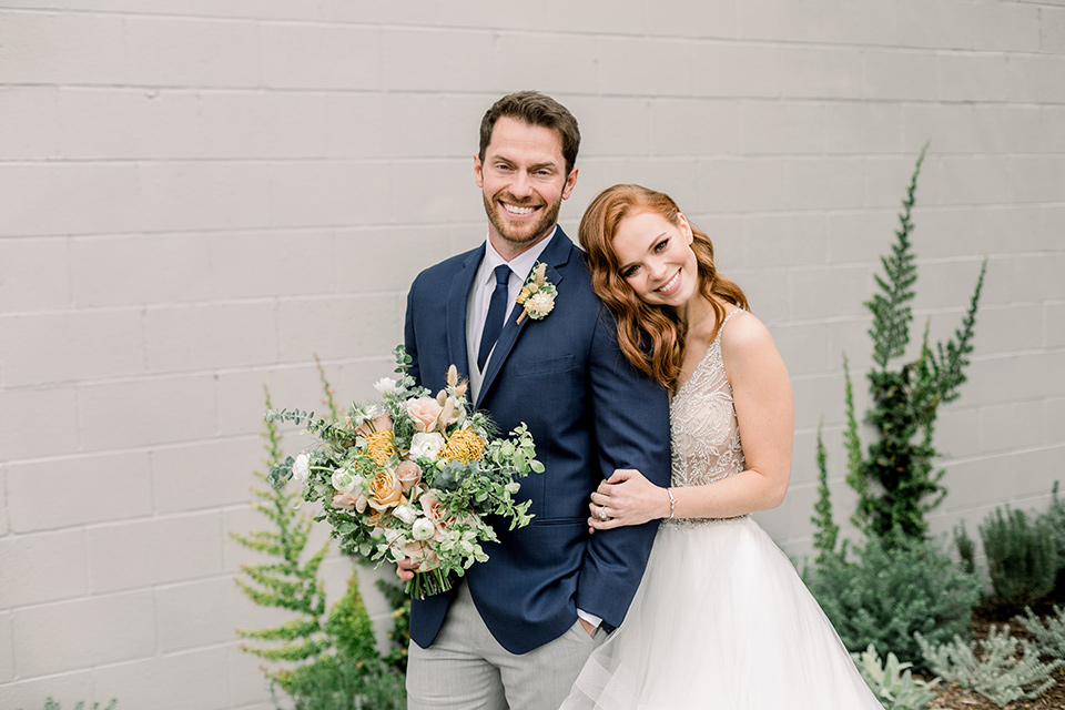 The-Harper-Shoot-bride-resting-head-on-groom-bride-in-a-tulle-ballgown-with-a-beaded-bodice-groom-in-a-mix-and-match-look-with-a-blue-jacket-and-grey-pant-and-vest-and-a-blue-long-tie-to-match-the-jacket