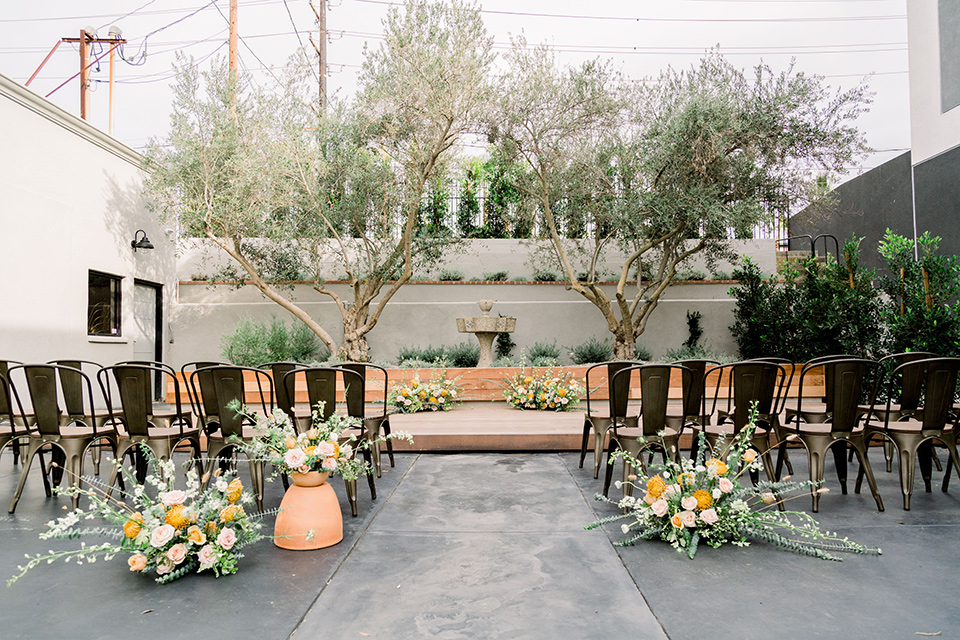 The-Harper-Shoot-ceremony-set-up-with-iron-and-wooden-chairs-and-simple-flowers