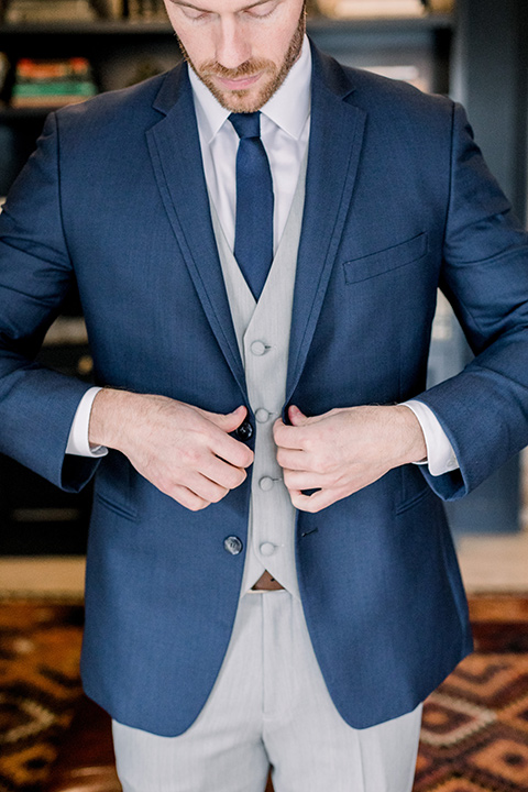 The-Harper-Shoot-groo-buttoning-jacket-groom-in-a-mix-and-match-look-with-a-blue-jacket-and-grey-pant-and-vest-and-a-blue-long-tie-to-match-the-jacket