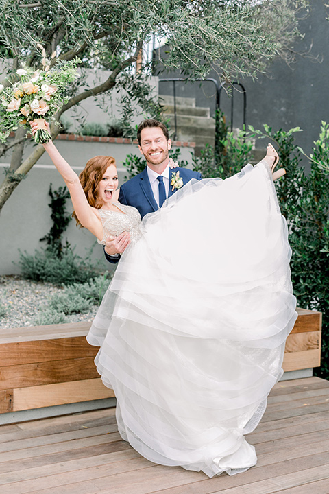 The-Harper-Shoot-groo-holding-up-bride-bride-in-a-tulle-ballgown-with-a-beaded-bodice-groom-in-a-mix-and-match-look-with-a-blue-jacket-and-grey-pant-and-vest-and-a-blue-long-tie-to-match-the-jacket