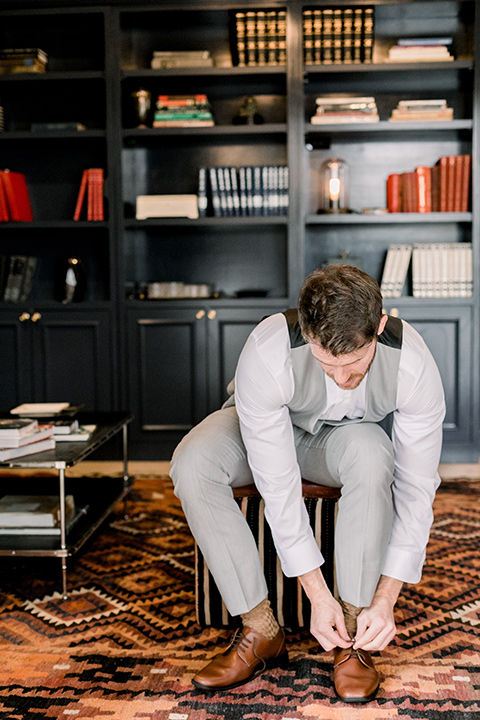 The-Harper-Shoot-groom-tying-shoes-in-a-light-grey-pant-and-vest-combo