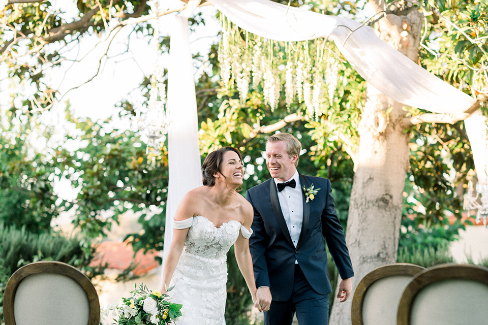 Inn-at-Rancho-Santa-Fe-wedding-bride-and-groom-after-ceremony-bride-in-a-formfitting-lace-gown-with-off-the-shoulder-sleeve-detailing-and-the-groom-in-a-navy-blue-tuxedo-with-a-shawl-lapel-and-black-bow-tie