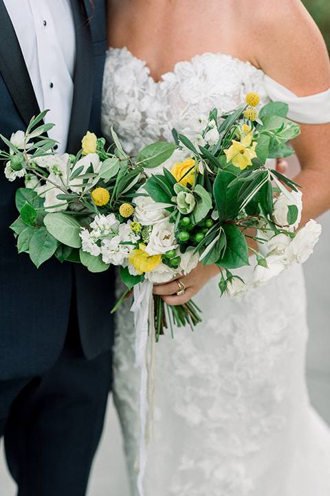 Inn-at-Rancho-Santa-Fe-wedding-bride-and-groom-close-up-holding-flowers-bride-in-a-formfitting-lace-gown-with-off-the-shoulder-sleeve-detailing-and-the-groom-in-a-navy-blue-tuxedo-with-a-shawl-lapel-and-black-bow-tie